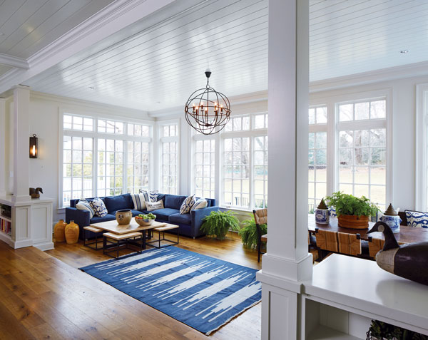 A Sitting Area Off The Kitchen Has Large Blue Sectional That Ties In With Of Table And Chairs Adjacent Dining