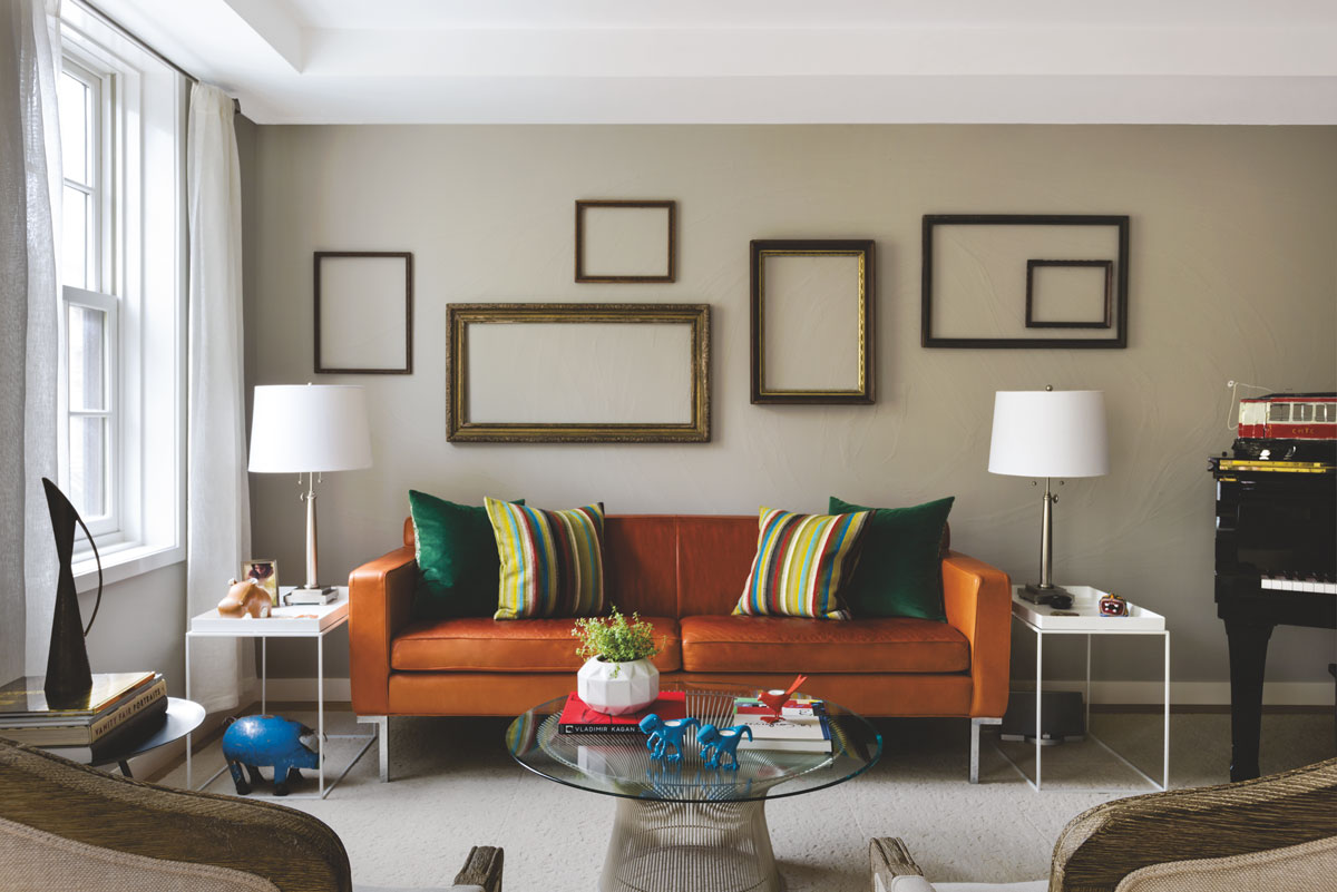 Living room an orange leather sofa with polished nickel legs brings color to the living room